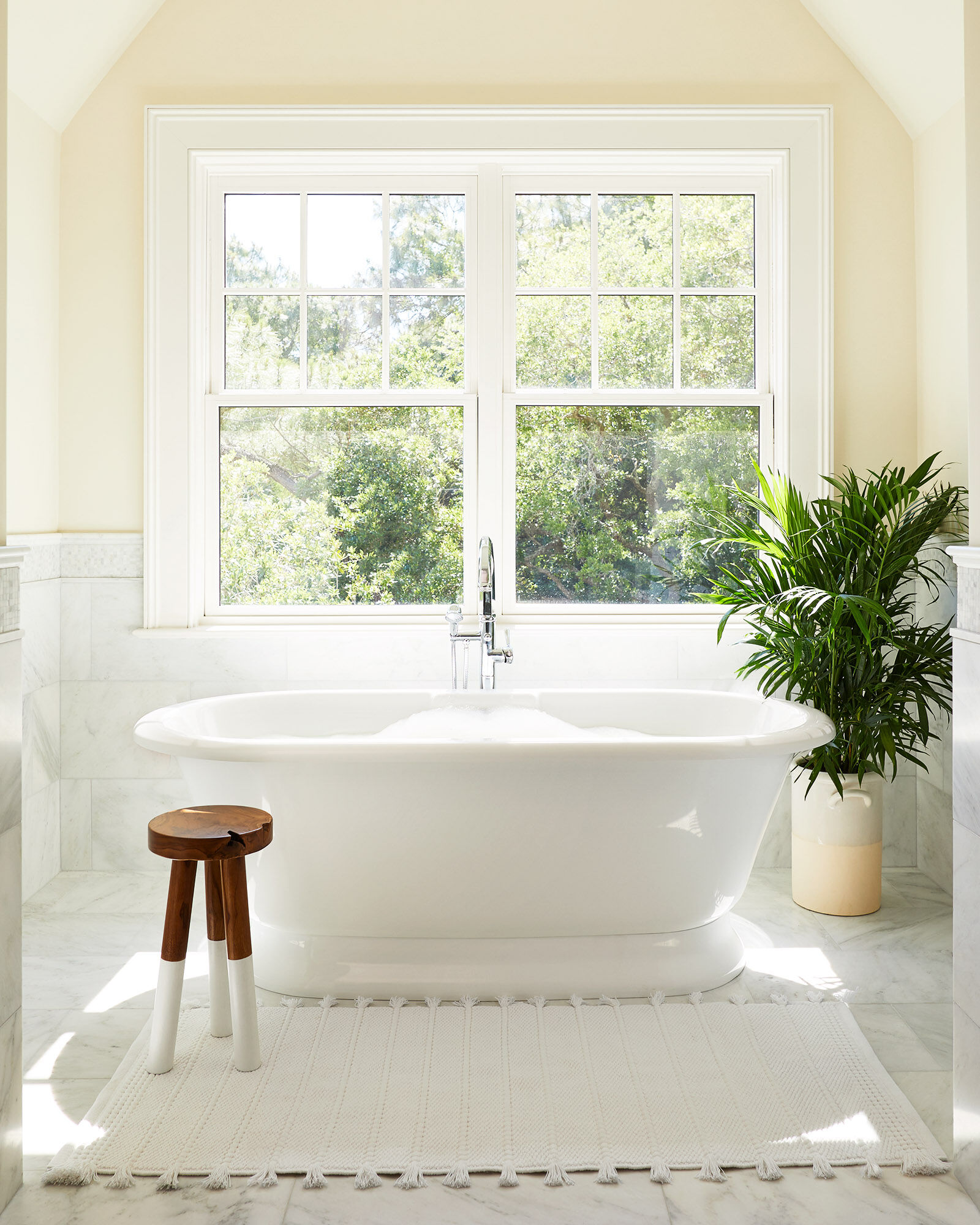 Dip-dyed stool next to soaker tub in luxurious white marble bath - Serena & Lily.