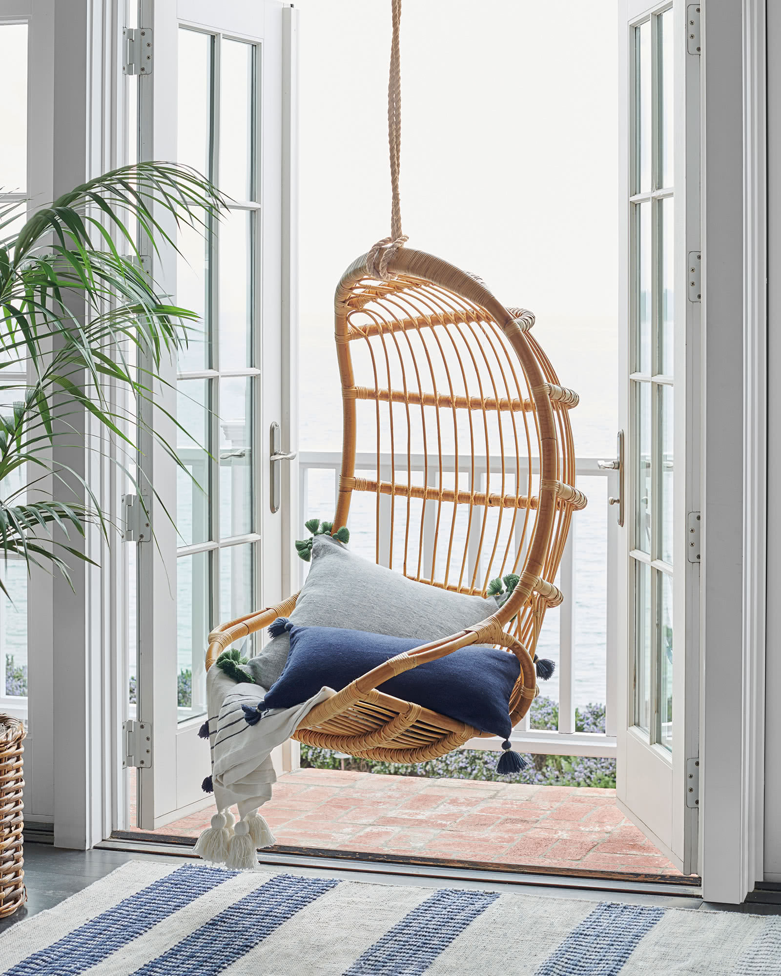 Hanging rattan chair in a glorious coastal home with French doors opening to a waterfront balcony.
