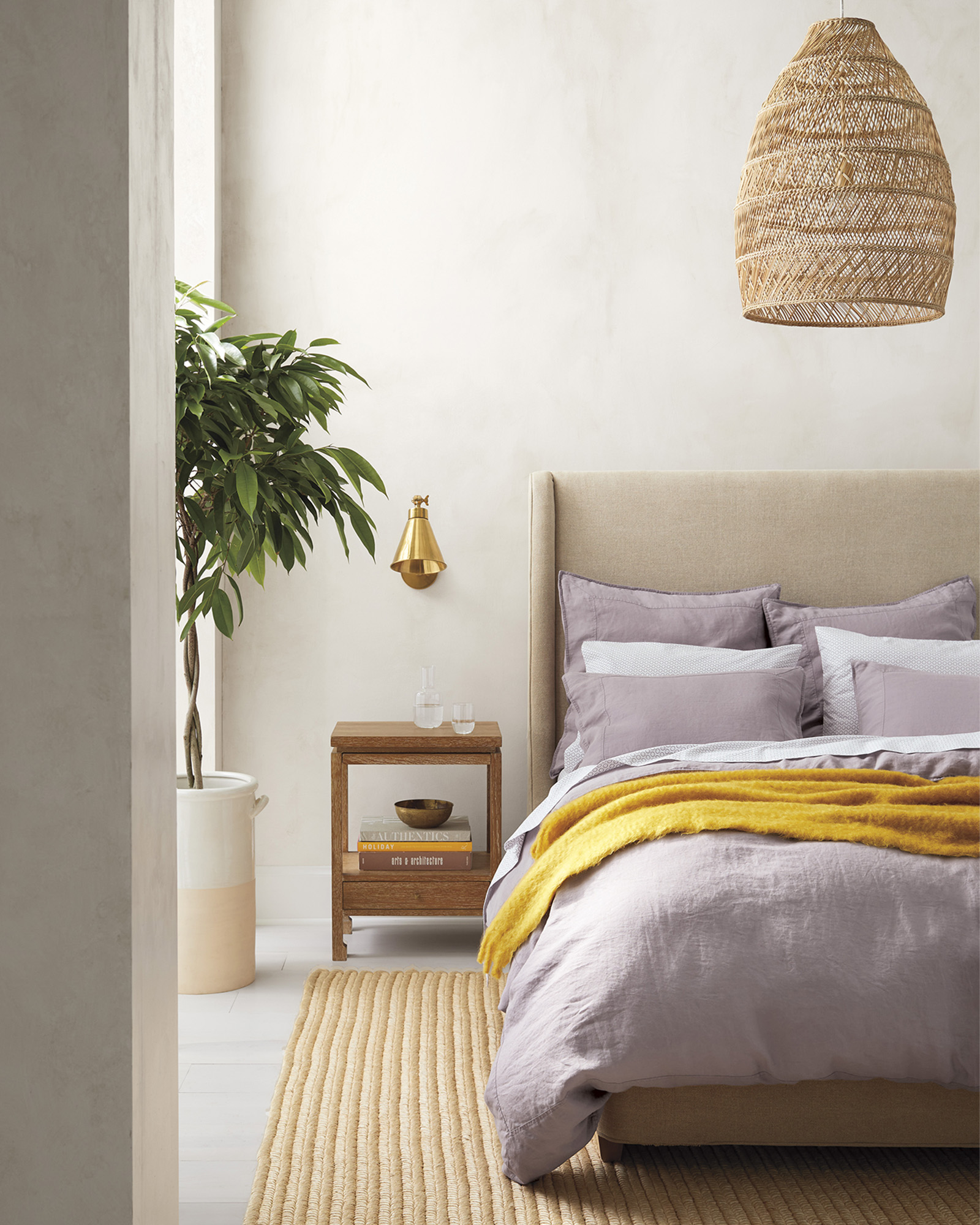 Headlands Bell Pendant from Serena & Lily in a bedroom with earthy neutrals and vibrant gold throw.