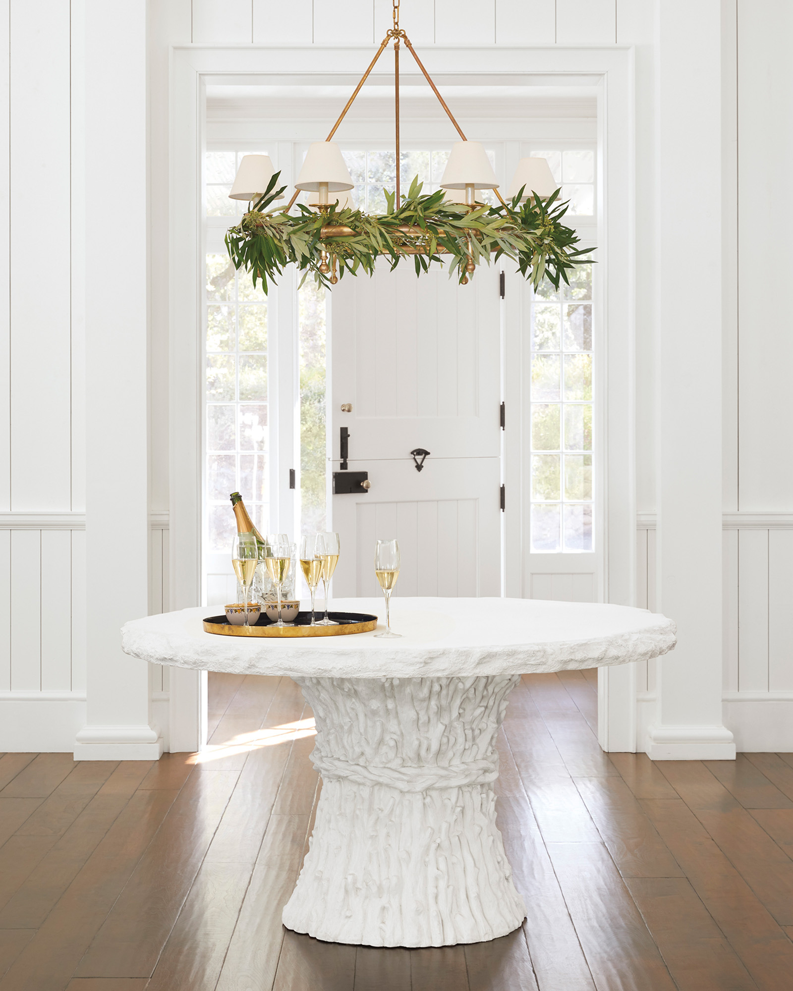 White faux bois table and greenery flocked chandelier in an all white entry of a coastal home - Serena & Lily.