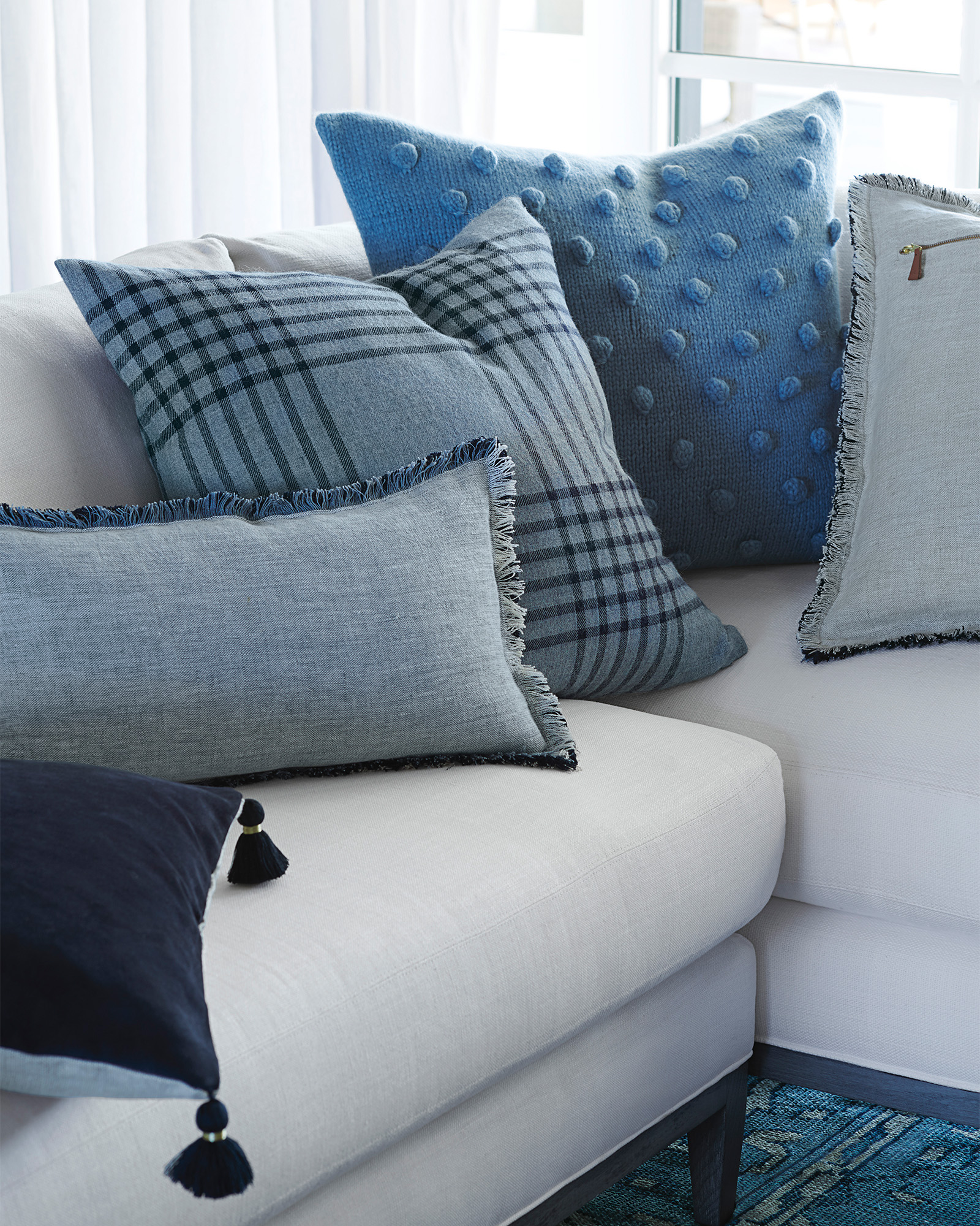 Blue pillows on a sofa (Blakely Plaid Pillow Cover) - Serena & Lily