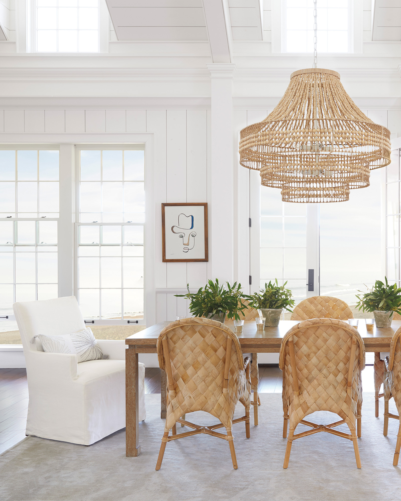 Coastal chic in a dining area with white on white decor, lofty ceilings, and natural woven texture on chandelier and chairs - Serena & Lily.